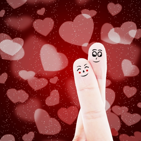 Finger lover on red background with heart shapes photo