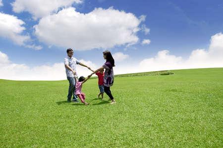 familia en jardin: Familia asi�tica feliz que juega en el campo Ellos se est�n ejecutando en el c�rculo de tiro sobre el cielo azul Foto de archivo