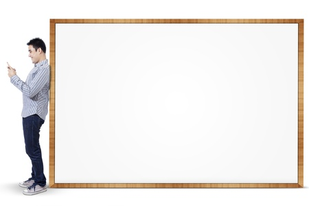 Smiling asian man holding smart phone standing at blank board photo