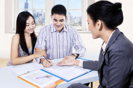 Young couple signing for financial contract with businesswoman photo