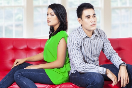 Young couple sitting on the couch not speaking after a fight in the living room Stock Photo - 22173099