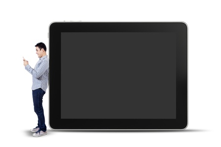 Young man using a mobile phone and standing next to big tablet isolated on white background photo