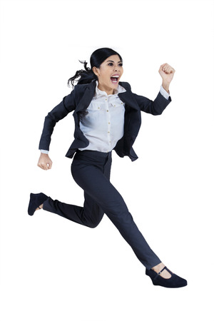 late: Business woman running in suit in full body isolated on white background  Stock Photo