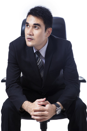 Asian businessman sitting on office chair looking at copyspace photo