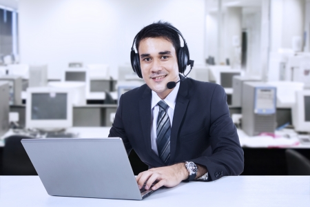 computer operator: Portrait of happy smiling customer support phone operator in headset at office