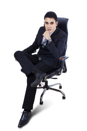 arm chair: Young Asian Businessman Sitting On Chair Over White Background Stock Photo