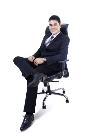 arm chairs: Asian Businessman sitting on office chair isolated over white