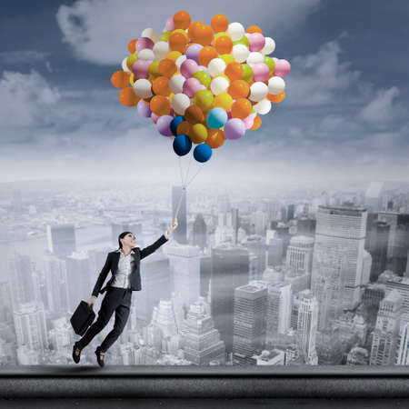 baloon: Beautiful young businesswoman flying with balloons over cityscape Stock Photo