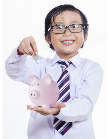 indian money: Happy boy puts the coin into a piggy bank isolated on white Stock Photo