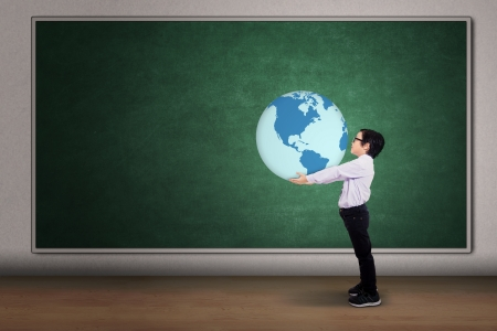 Asian boy holding a globe on the classroom photo