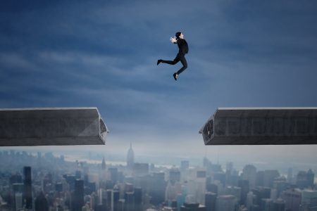 interrupted: Young businesswoman jumping over a gap in the bridge over cityscape
