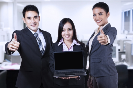 Young business people showing blank screen on laptop and thumbs up photo