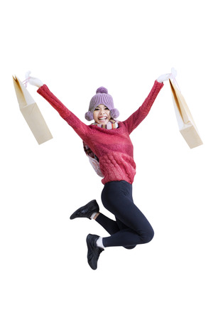 Young woman jumping with shopping bags isolated on white background photo