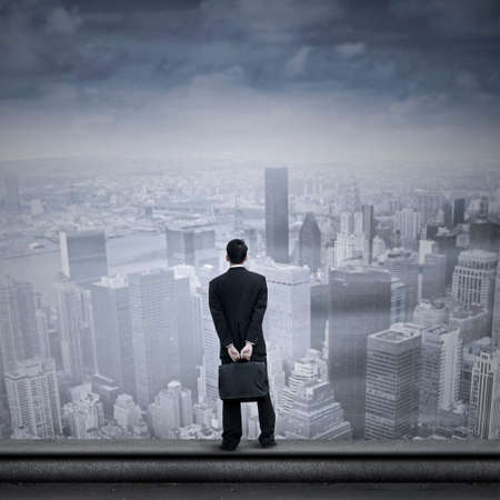 Portrait of a businessman looking into the future standing on the top of a skyscraper photo