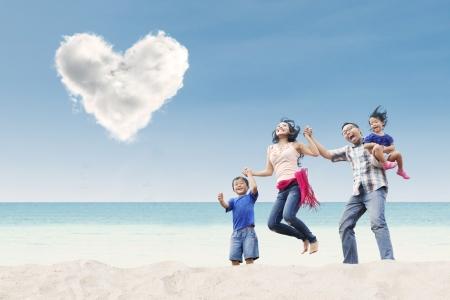 under heart: Asian family jumping under heart cloud on the beach