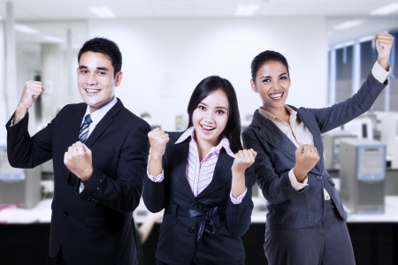 personas festejando: Hombres de negocios acertados que celebran un triunfo con los brazos en la oficina