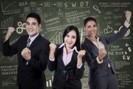 excited business woman: Successful business team celebrating their triumph with arms up
