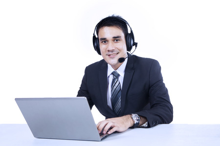 Smiling businessman working with laptop and headset photo