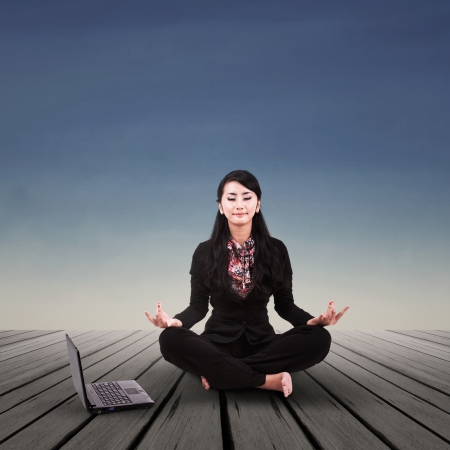 Asian businesswoman is meditating outdoor photo