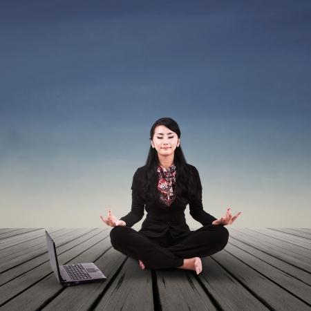mujer meditando: Empresaria asi�tica est� meditando al aire libre Foto de archivo