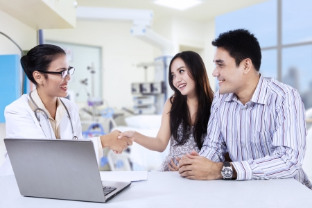 doctor laptop: Asian female doctor handshake with pregnant woman in doctor Stock Photo