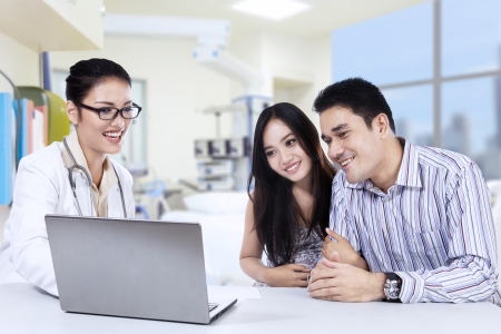 Female doctor looking a laptop with pregnant woman and her husband in clinic photo