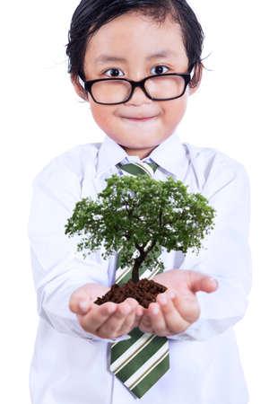 educacion ambiental: Niño pequeño con la planta en las manos, aislados en fondo blanco Foto de archivo