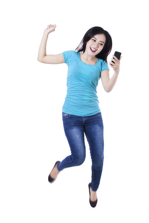 Happy asian woman holding cellphone and jumping for joy photo