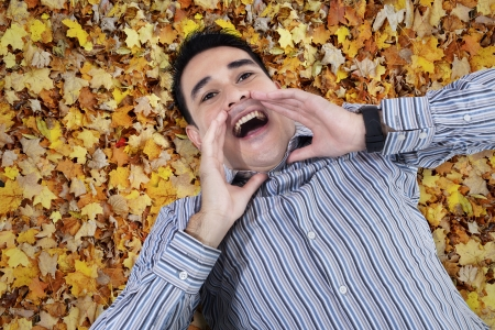 Asian young man shouting on autumn leaves ground photo