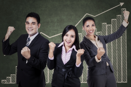 profit celebration: Successful business team celebrating their triumph with graph on chalkboard Stock Photo