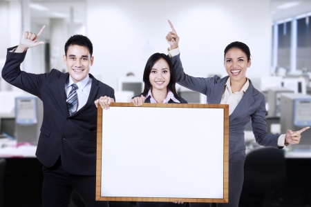 Group of business people holding empty board in office photo
