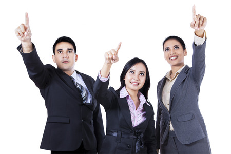 Group of young business people standing together pointing and looking up photo