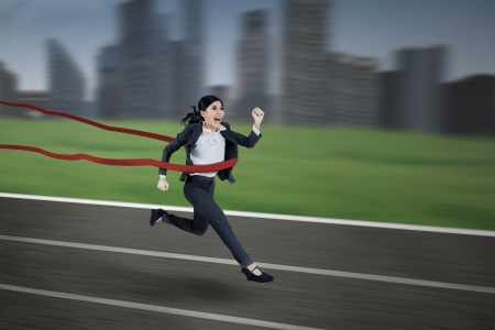 Asian businesswoman winning the race with the city skyscrappers in the background photo