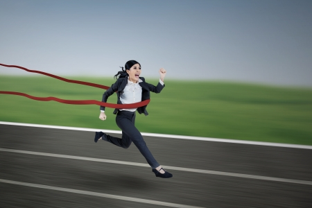 Beautiful young businesswoman passing finishing line photo