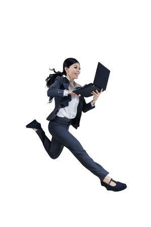 Excited woman running and holding a laptop on white background photo