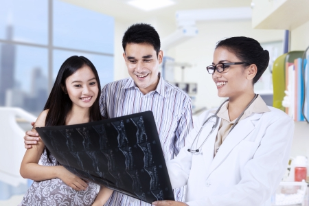 indonesian woman: Healthcare and medical concept - doctor with patients looking at x-ray