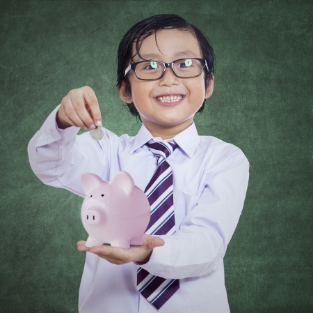 Happy boy puts the coin into a piggy bank on chalkboard background photo