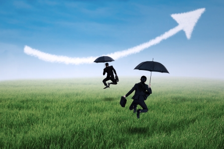 Happy insurance agent jumping with umbrella and arrow up on the meadow photo