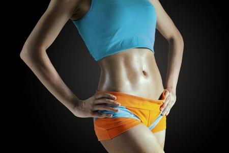 abdomen plano: Parte del cuerpo de la hembra atractiva en fondo oscuro