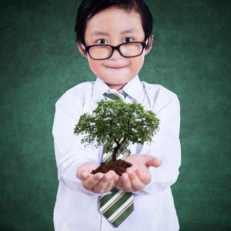 educacion ambiental: Muchacho elegante con la planta verde en el aula