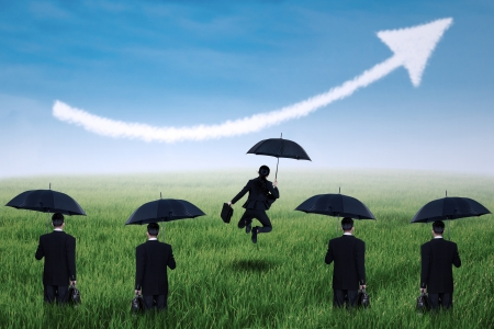 Successful  businesswoman with umbrella and arrow up on the meadow photo