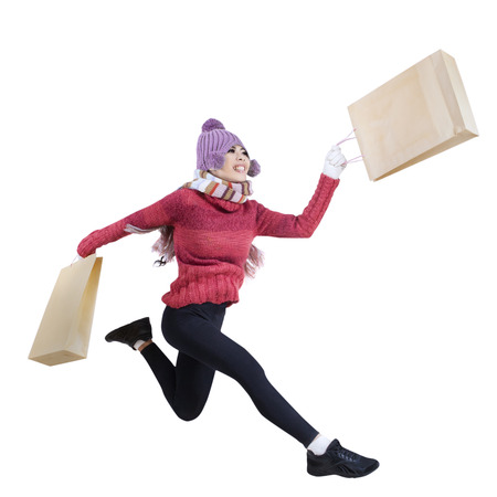 happy shopper: Winter woman running and holding shopping bags isolated on white background Stock Photo