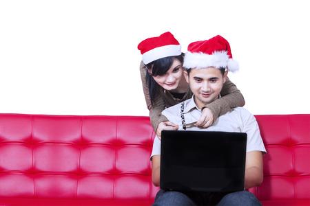 Young hispanic couple christmas shopping online isolated on white background photo