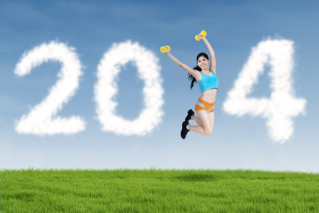 Happy fitness woman jumping and 2014 New Year clouds outdoor photo