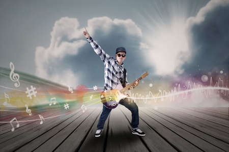 korean man: Artist perform guitar instrument under blue sky with musical notes  Stock Photo