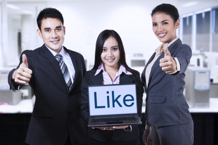 Group of business people showing like on laptop and thumbs up