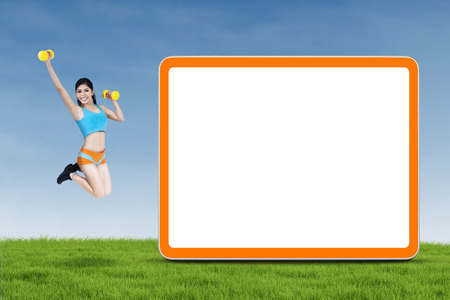 Athletic woman jumping with dumbbell next to empty board photo