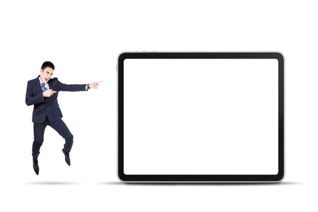 Happy asian businessman jumping and pointing a digital tablet photo
