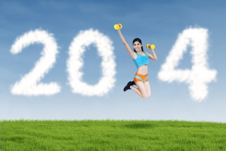 Happy fitness young woman jumping with new year 2014 of clouds photo