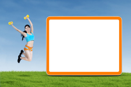 Happy fitness young woman with dumbbells jumping next to blank board photo